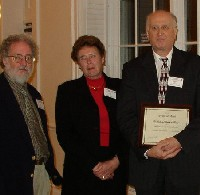 John Revitte (left) presented the Award of Merit to Betty LeClair (President) and C. Edward Wall (holding plaque)