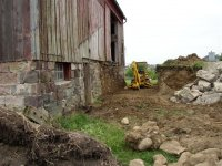 Removing the silo and barn ramp to provide access to the north foundation wall.